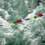 Prayer flags over water.